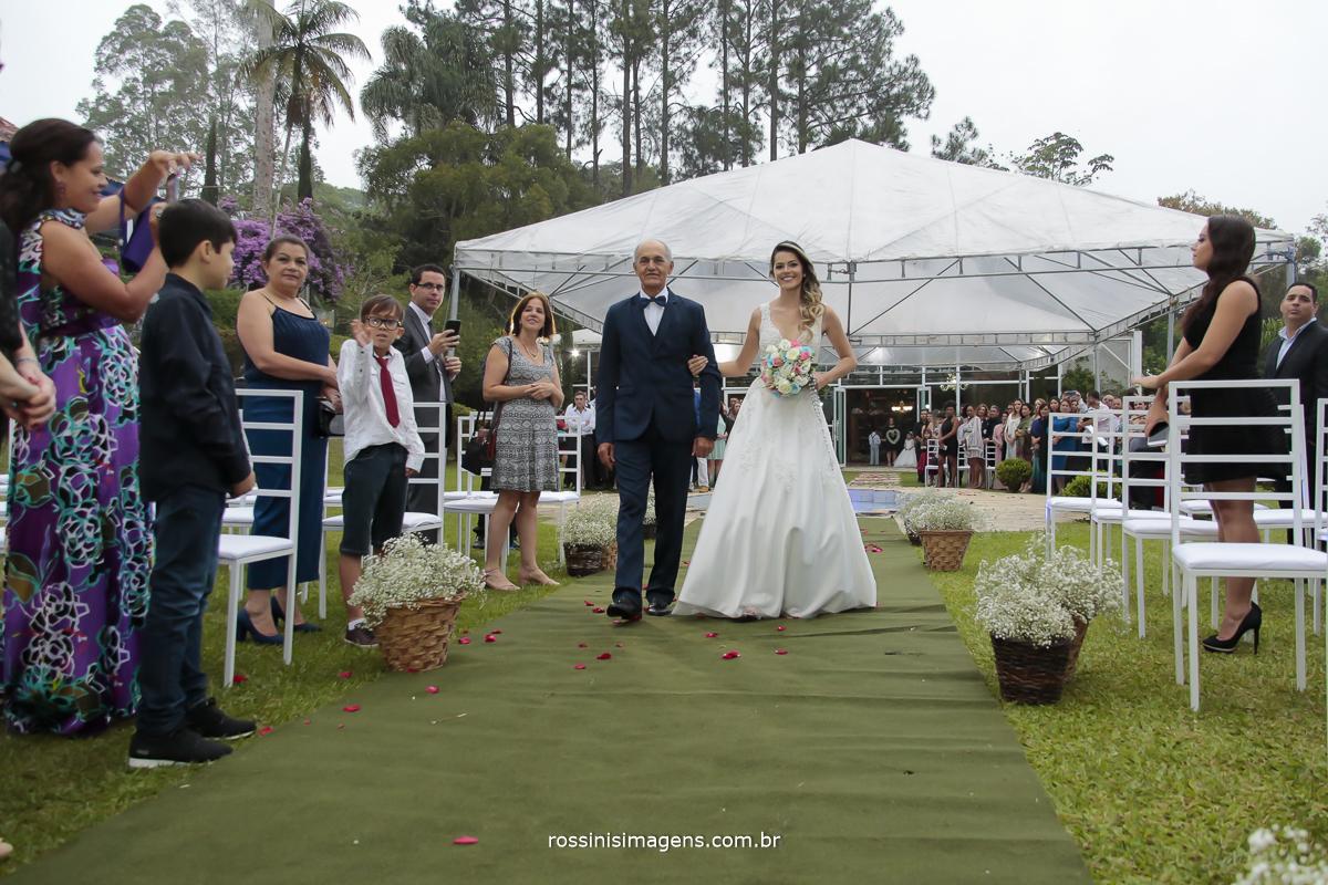 entrada da noiva no tapete ao ar livre no dia maravilhoso, noiva sendo conduzida por seu pai de camisa branca, gravata borboleta azul, terno e calça azul , a felicidade no olhar da noiva de branco com o lindo buquê de flores