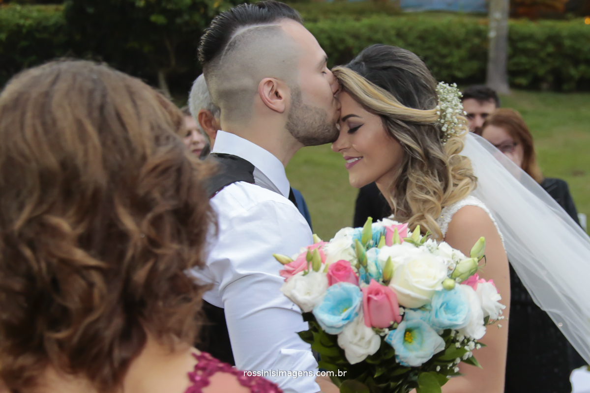 imagem de pais e padrinhos emocionados com a  recepção do noivo com um singelo beijo na testa da sua noiva, que esta com o sorriso estampado no rosto de felicidade, realização do casamento