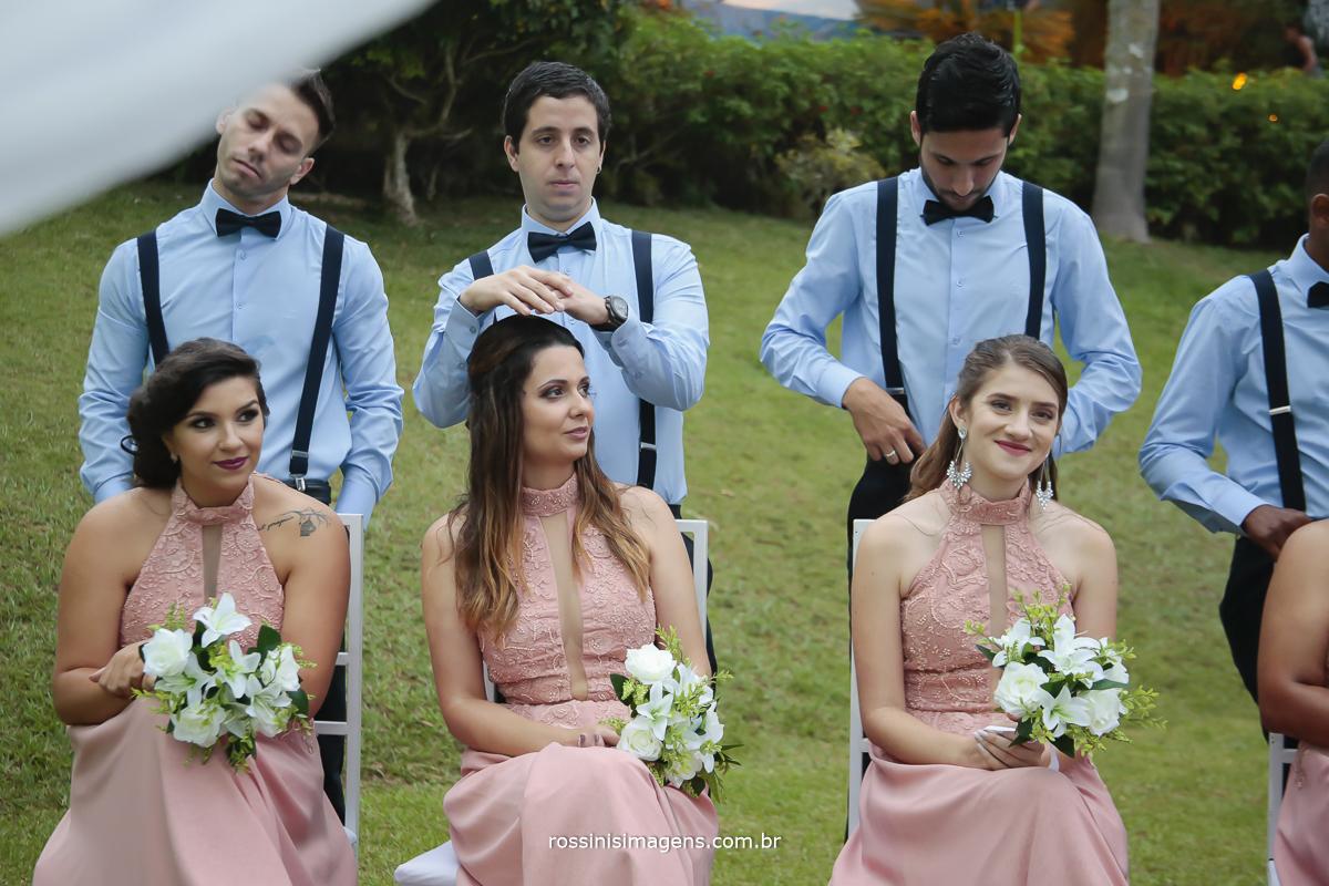 fotografia dos padrinhos de camisa azul gravata borboleta e suspensório e as madrinhas sentadas com vestidos rosé longo