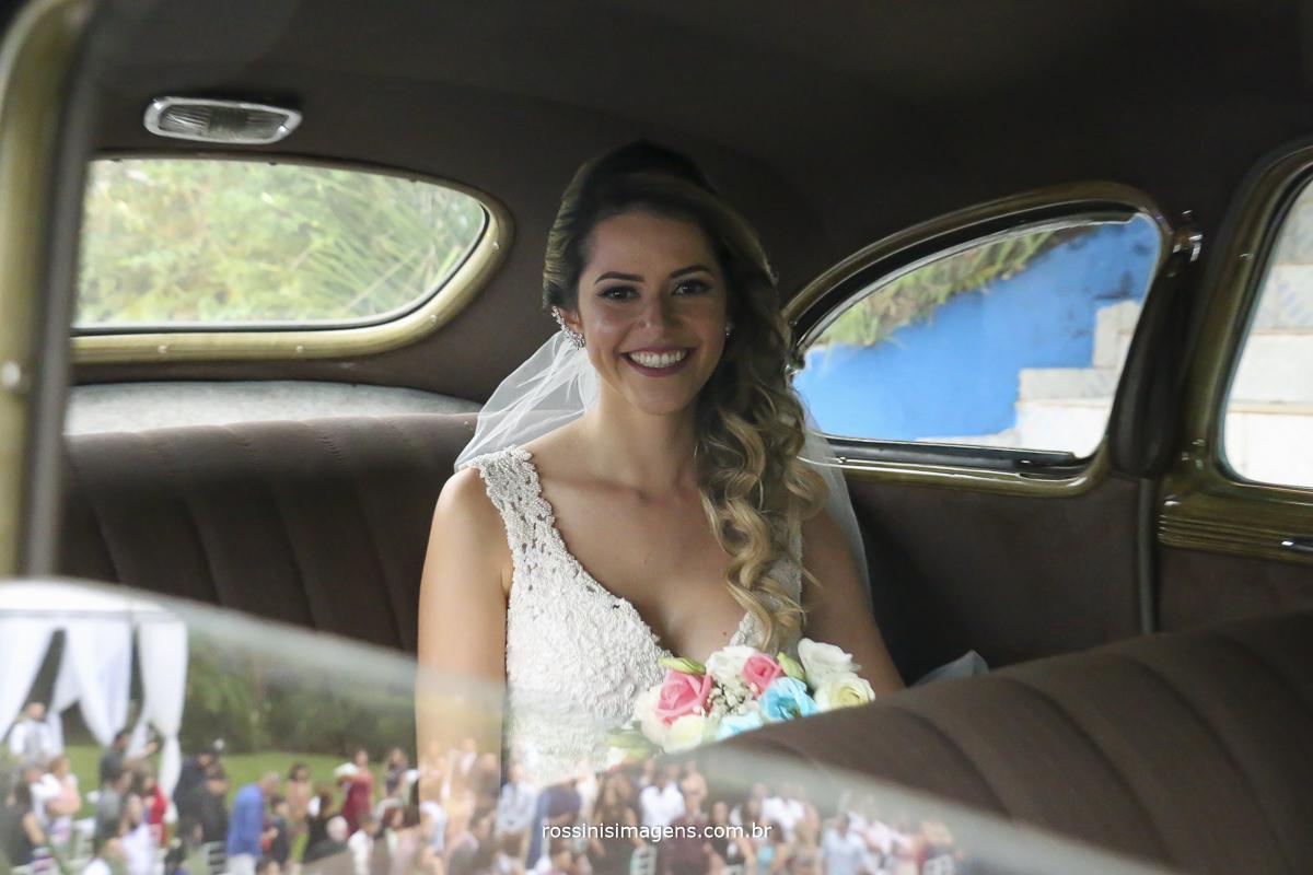 foto feliz da noiva no carro sorrindo com o buquê, e o incrível reflexo do local da cerimonia com os convidados e o noivo esperando a noiva para o cerimonial do casamento, que dia fantástico
