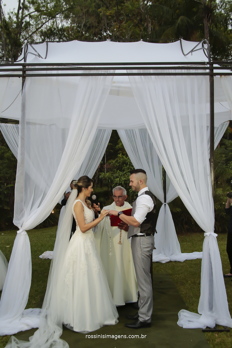 foto dos voltos do casamento da noiva para o noivo, noiva colocando a alianças