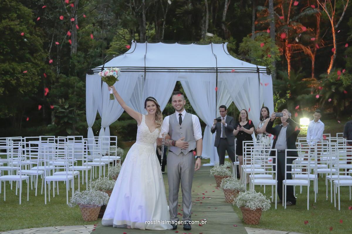 fotografia da saída dos noivos agora casados, cerimonia ao ar livre, chuva de pétalas de rosas vermelhas
