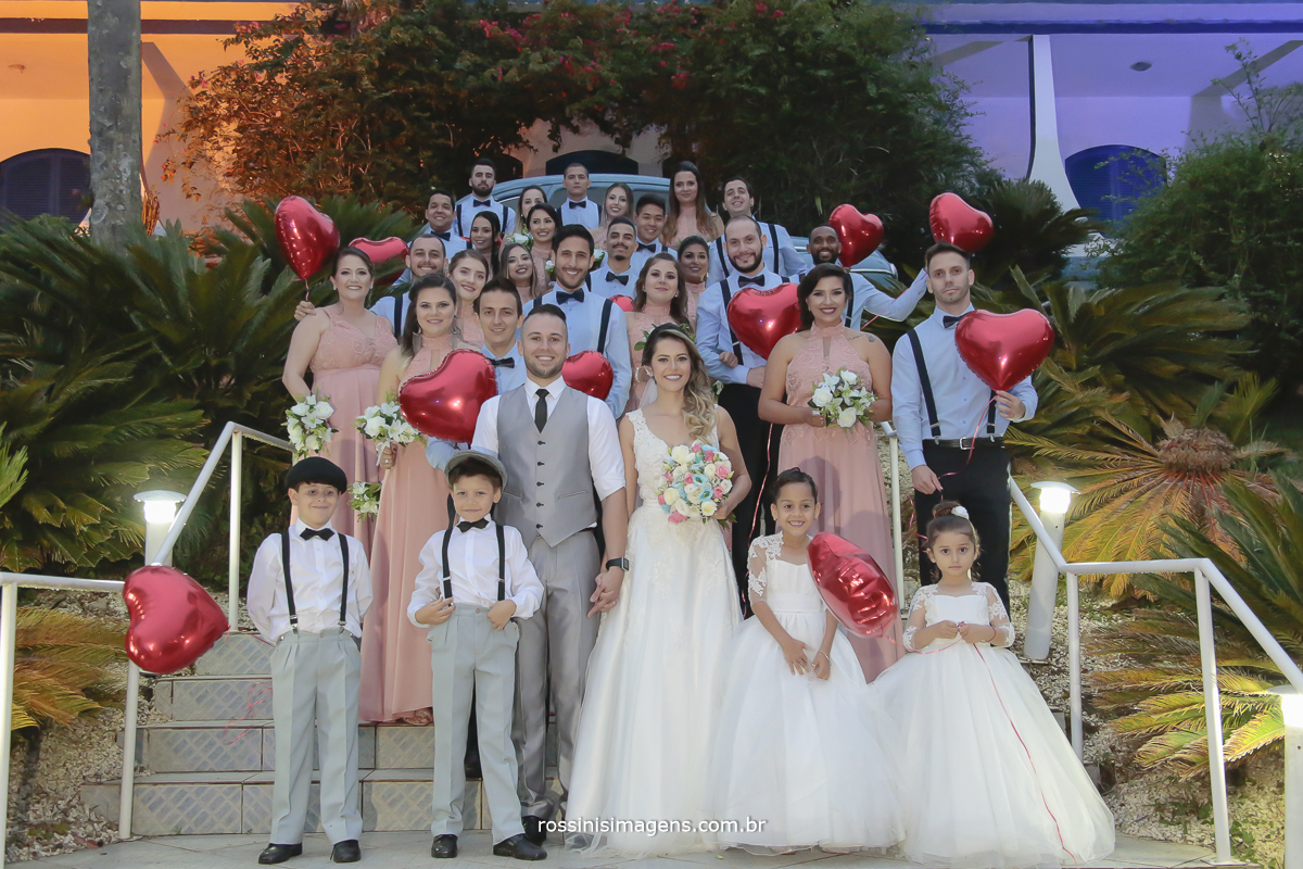 fotografia de casamento, foto coletivacom os padrinhos de azul com suspensório, madrinhas de vestido rosé, damas e pajens de roupa clara e o casal especial os noivos ao centro da foto