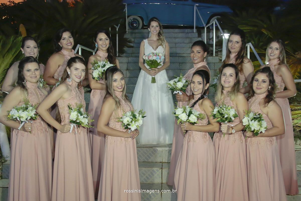 fotografia das madrinhas de vestido rosé segurando o buquês  e a noiva de branco ao centro da foto com o buquê de flores