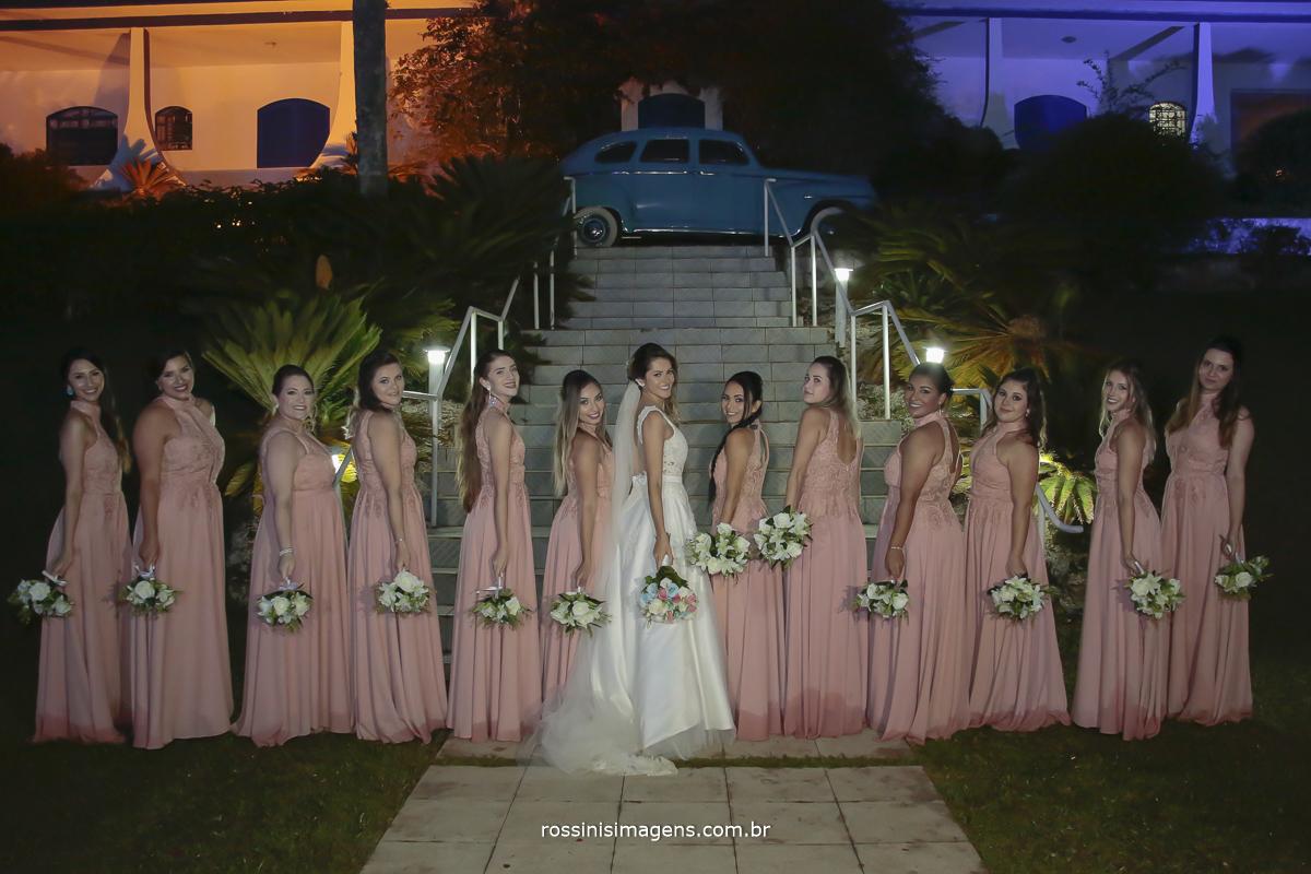 todas as madrinhas de vestidos rosé de lado mostrando o vestido e segurando o buquê e a noiva de vestido branco cheio de detalhes virada de lado com o buque na mão