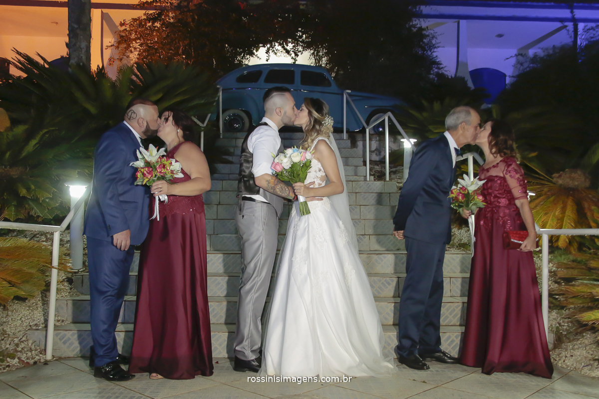 fotografia de família, fotografo de casamento em mogi das cruzes, pais do noivo, noivos e pais da noiva se beijando na foto depois da cerimonia do casamento