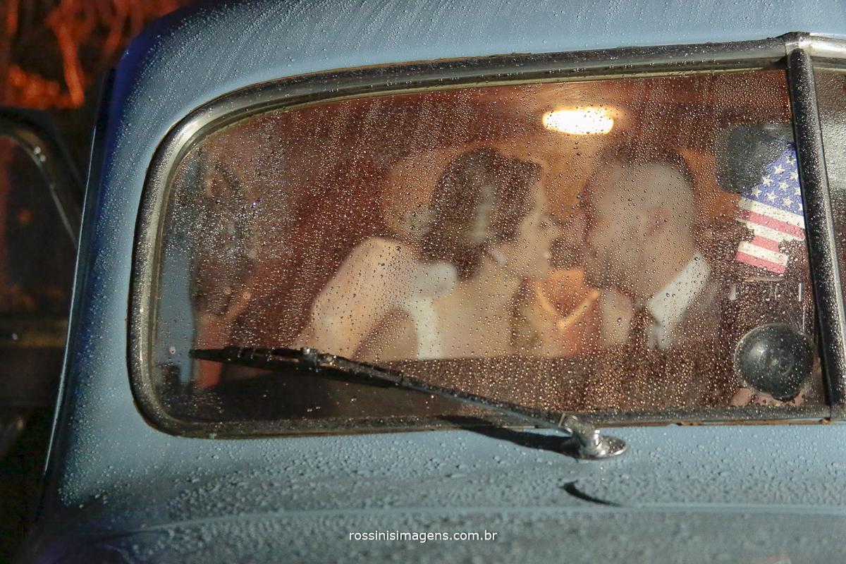 fotografia de noivos dentro de carro se olhando e vidro do carro molhando cheio de gotas de chuva, uma linda fotografia de casamento