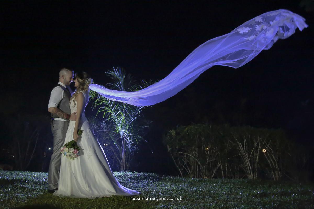fotografia do casal abraçados, noiva com o buquê e o véu voando refletindo a luz atrás deles azul no véu