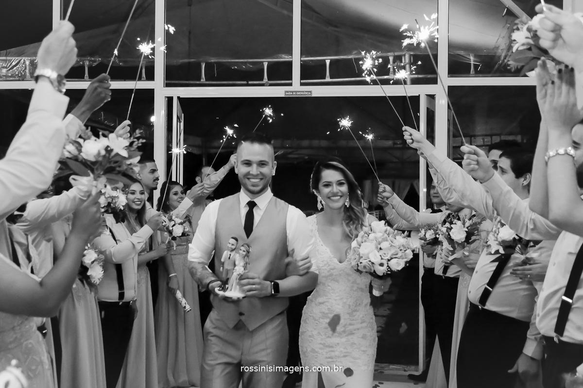fotografia entrada dos noivos com o buquê o o topo do bolo na recepção com padrinhos com buquês e muito sparks