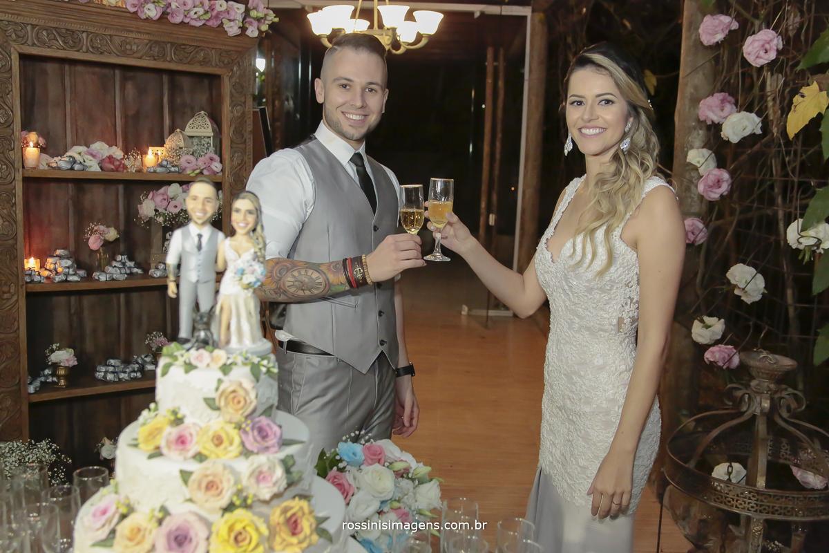 fotografia dos noivos na mesa do bolo com o topo de bolo personalizado fazendo um brinde a vida de casado e felizes