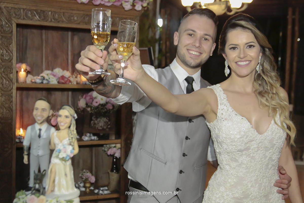 fotografia na mesa do bolo do casal oferecendo brinde aos convidados