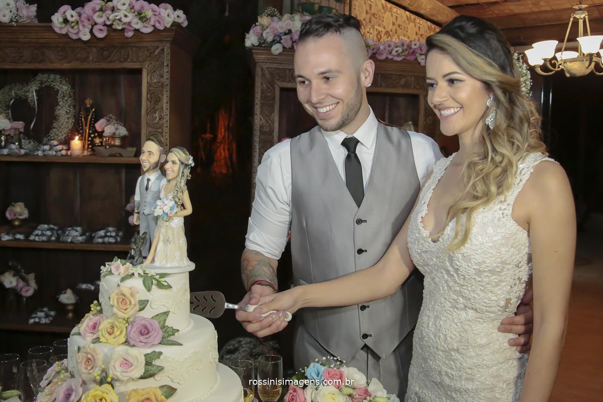 foto dos noivos olhando para o bolo e fazendo o corte do bolo com uma alegria e uma felicidade sem explicação