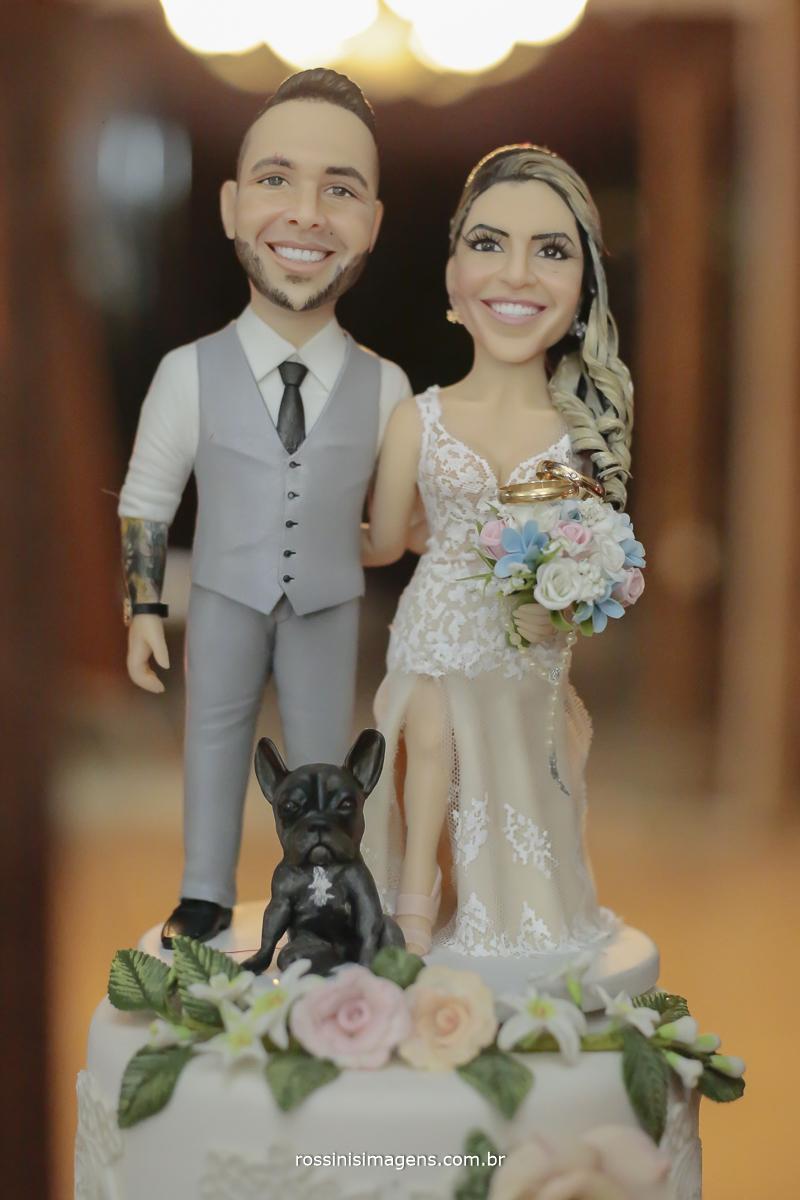 fotografia da aliança no topo do bolo personalizado com os noivos idênticos e com a cadelinha dory, pug frances