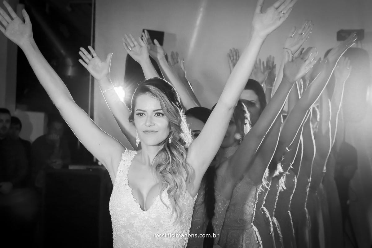 fotografia da dança da noiva com as madrinhas disputando com o noivo e os padrinhos, noiva e madrinhas em uma fila todas com as mãos para o alto