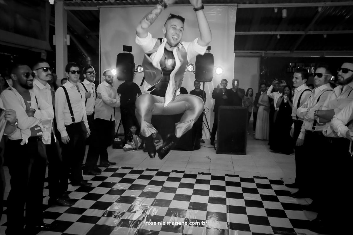 fotografia da dança dos noivo com os padrinhos na disputa com a noiva e as madrinhas, noivo dando uma sarrada no ar que todos os convidados não acreditaram