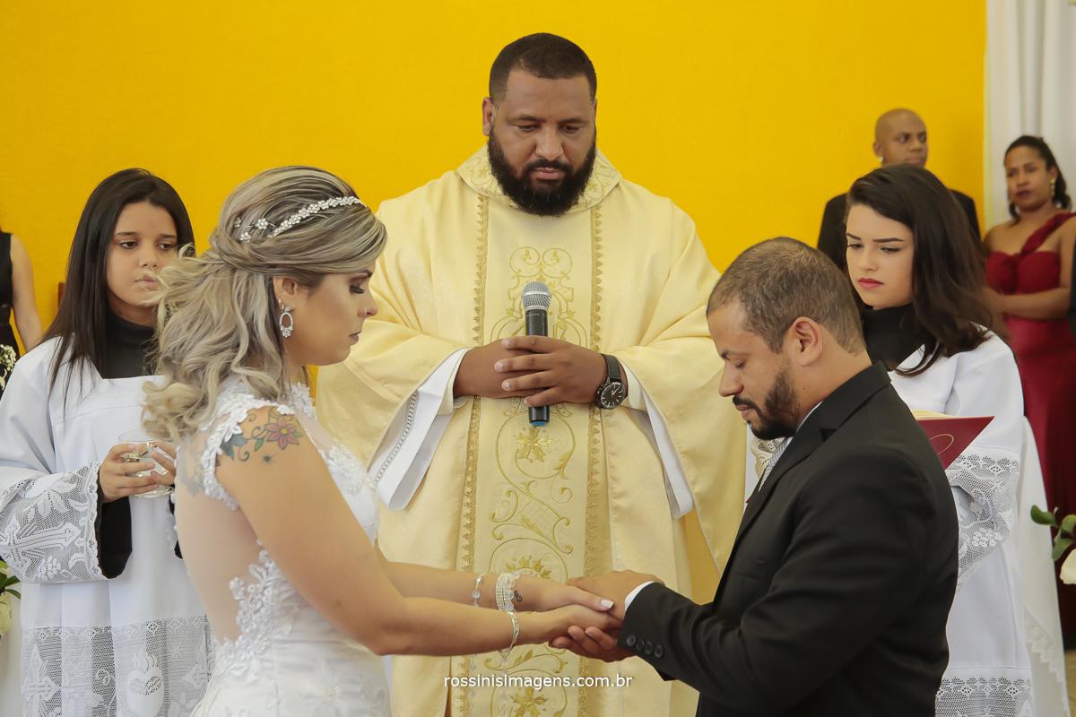 fotografia da benção das alianças no casamento da mariana e everton realizado na paroquia santa helena em Suzano são paulo dia de agradecer a deus