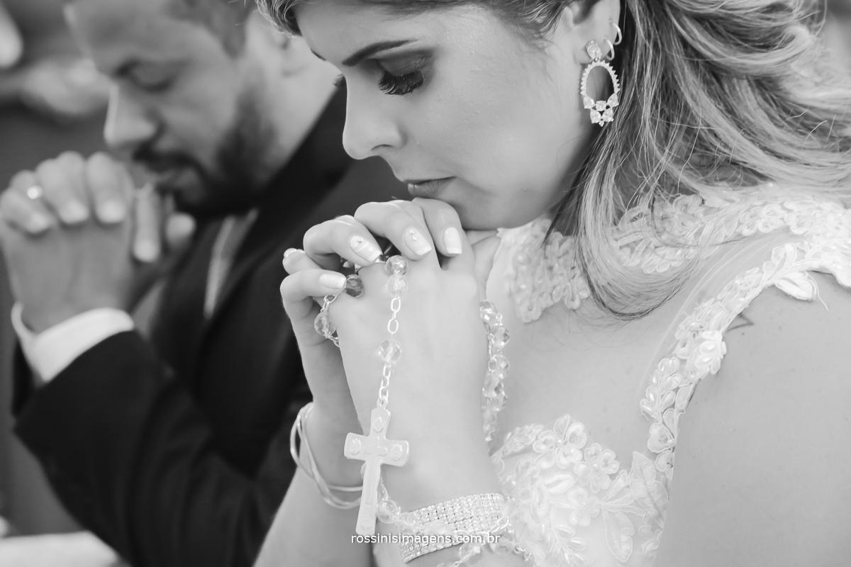 fotografia de casamento noiva e noiva de joelhos rezando juntos na igreja, noiva com terço