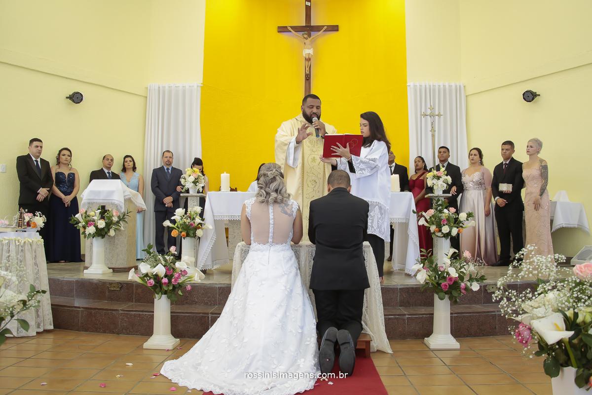 noivos ajoelhados no altar sendo abençoados pelo padre em uma linda cerimonia de casamento na igreja