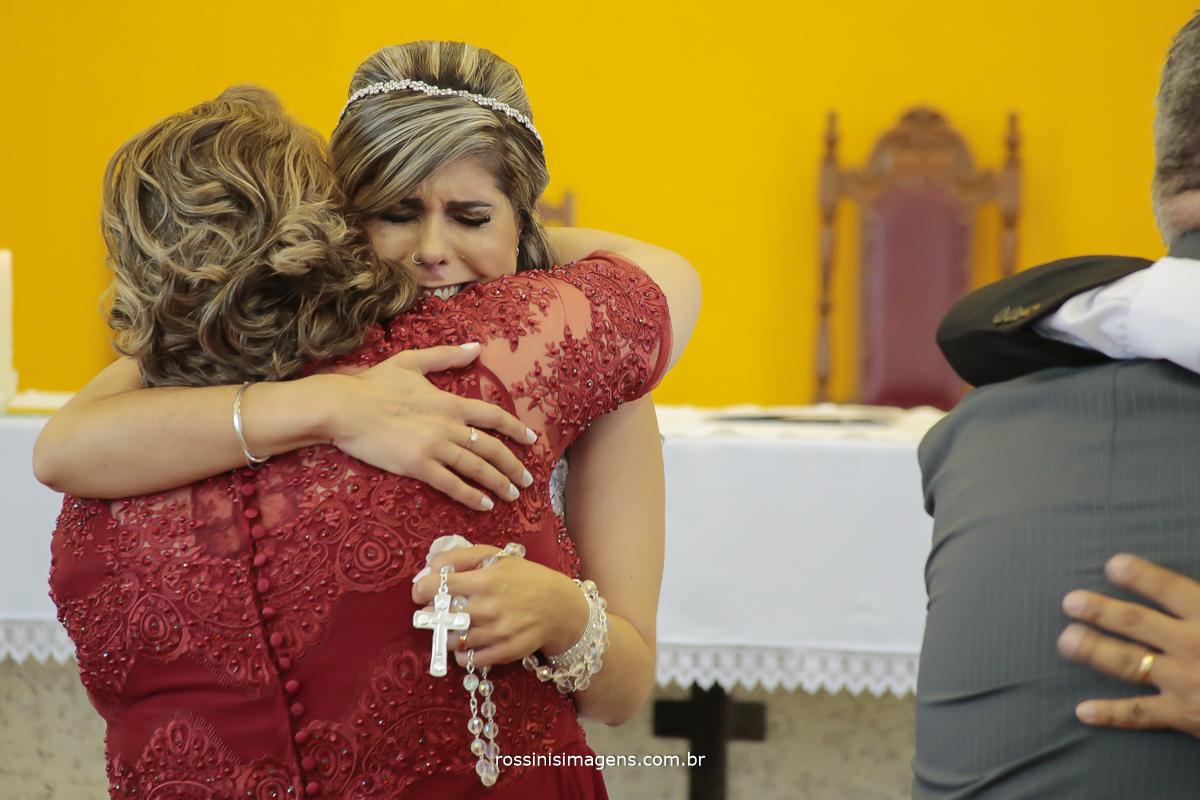 abraço da mãe da noiva em sua filha no altar no casamento