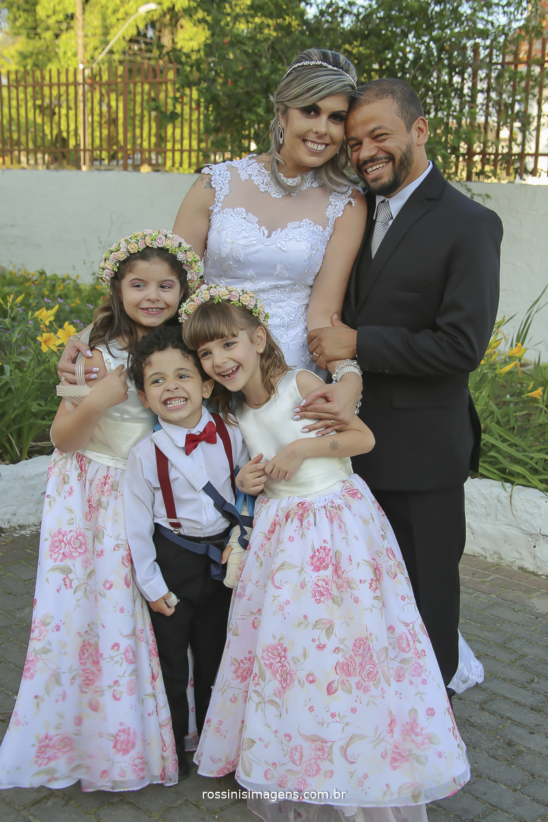 imagem dos noivos com as damas e o pajem no jardim da igreja