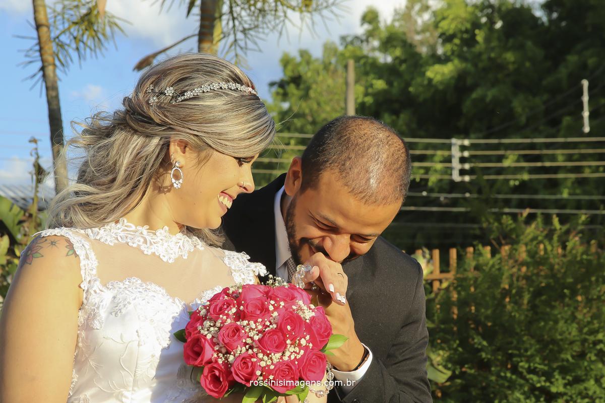 imagem do noivo beijando a mão da noiva que esta rindo muito feliz
