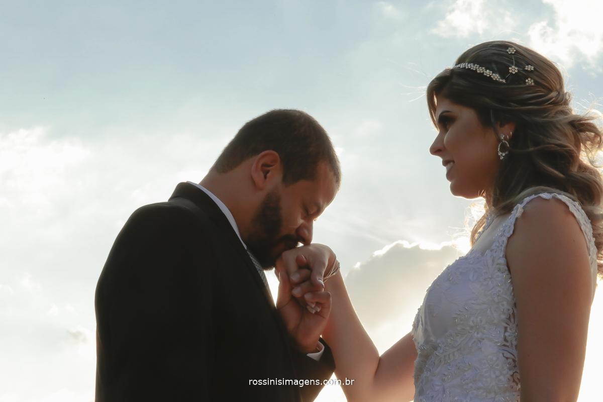 foto de casal no por do sol noivo beijando a mão da noiva