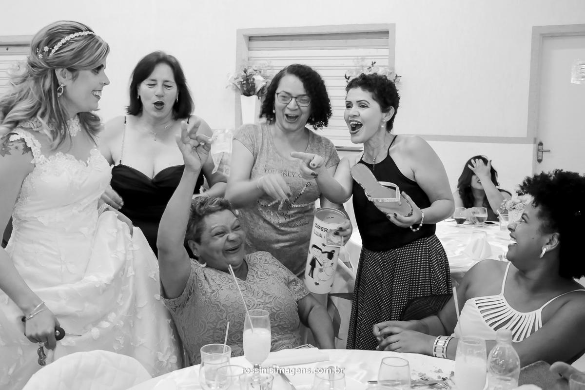 convidados ajudando o sapatinho da noiva para lua de mel