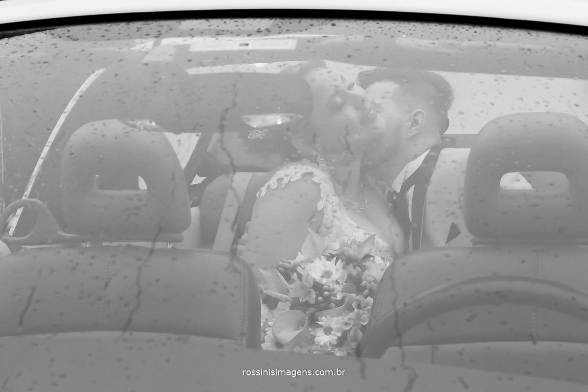 linda fotografia de casamento arte com os noivos no carro através do vidro do carro refletindo o sentimento de amor e conquista