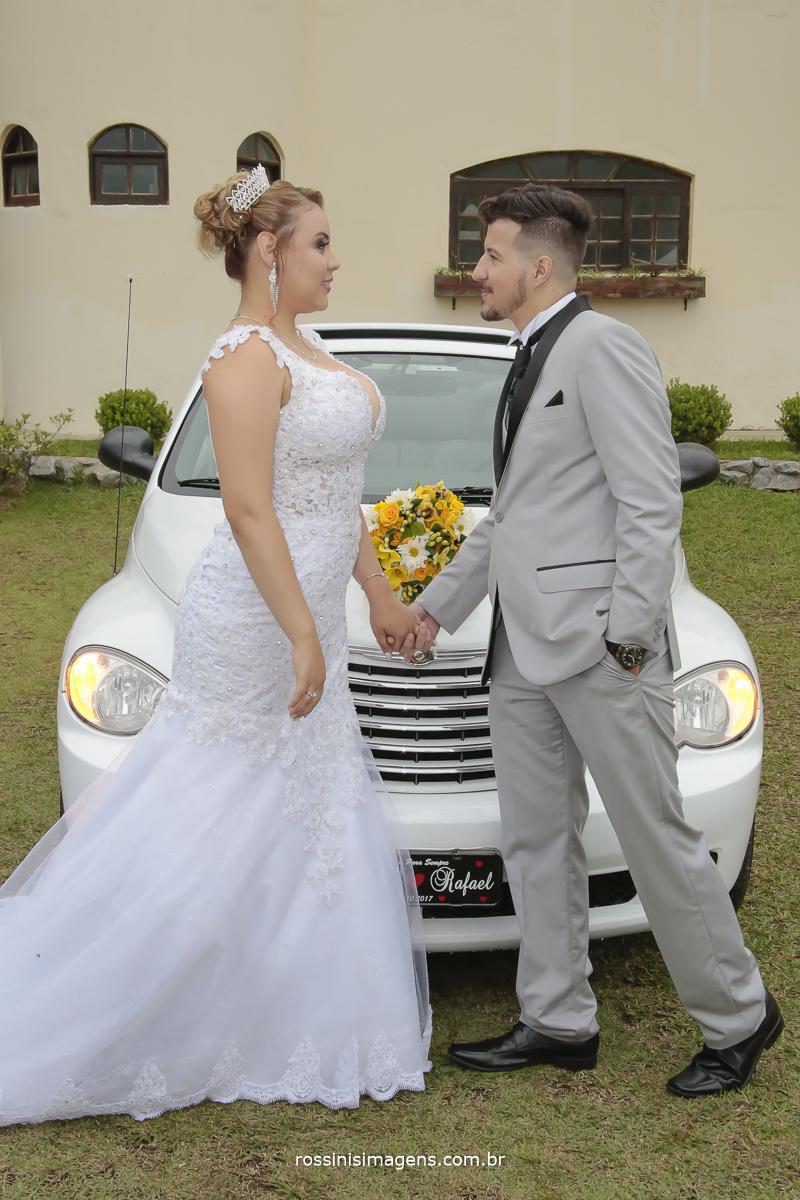 fotografia com o casal de noivos se olhando de maos dadas em frente o carro dos noivos pt Cruise branco