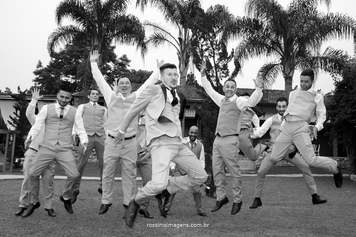 foto pb de casamento noivo com os padrinhos pulando dando a sarrada no ar