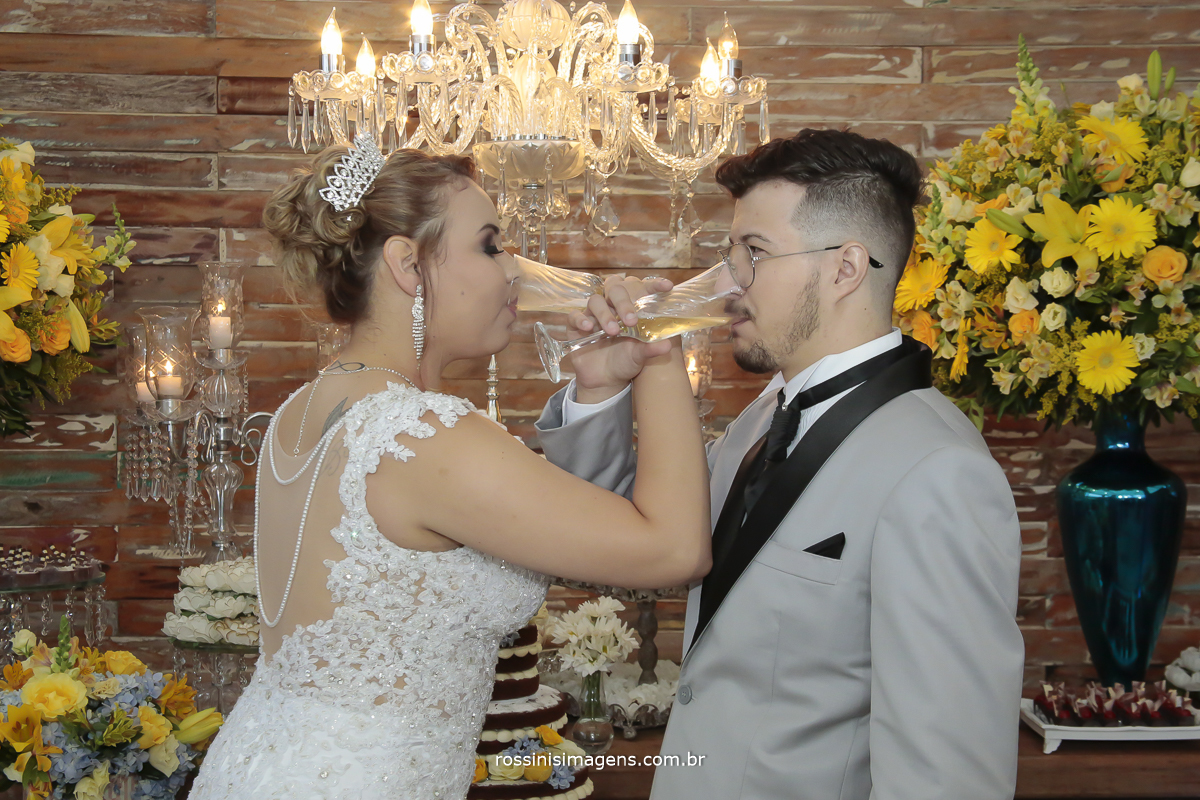 fotografia do brindo do casal na mesa do bolo lindos detalhas da mesa do bolo e do vestido da noiva