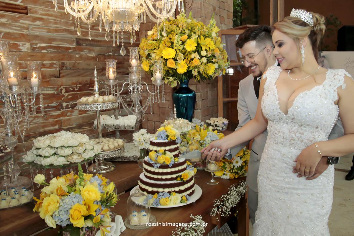 noivos na mesa do bolo simulando o corte do bolo um lindo e maravilho neked cake, casamento rafael e jessica