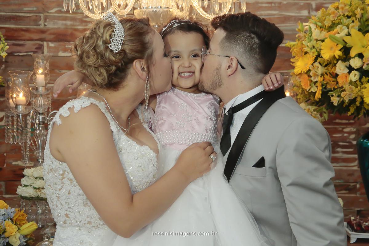 fotografia dos noivos com a daminha, noiva de branco, noivo de cinza, daminha de rosa