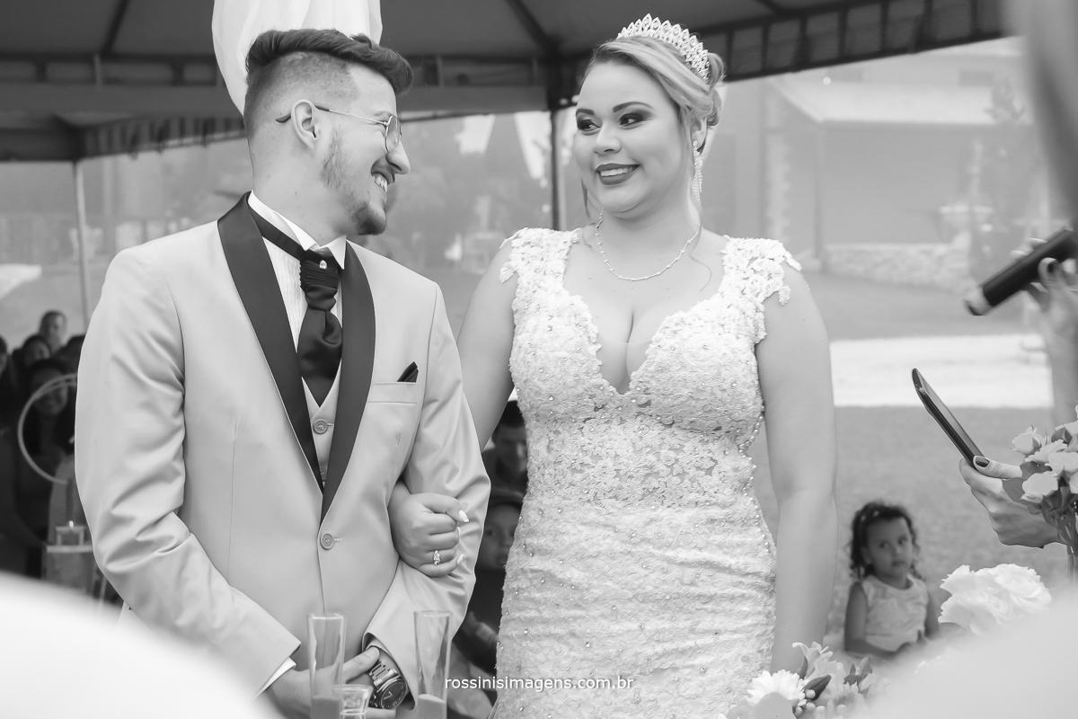 foto de casamento ao ar livre, noivo olhando para a noiva e rindo muito