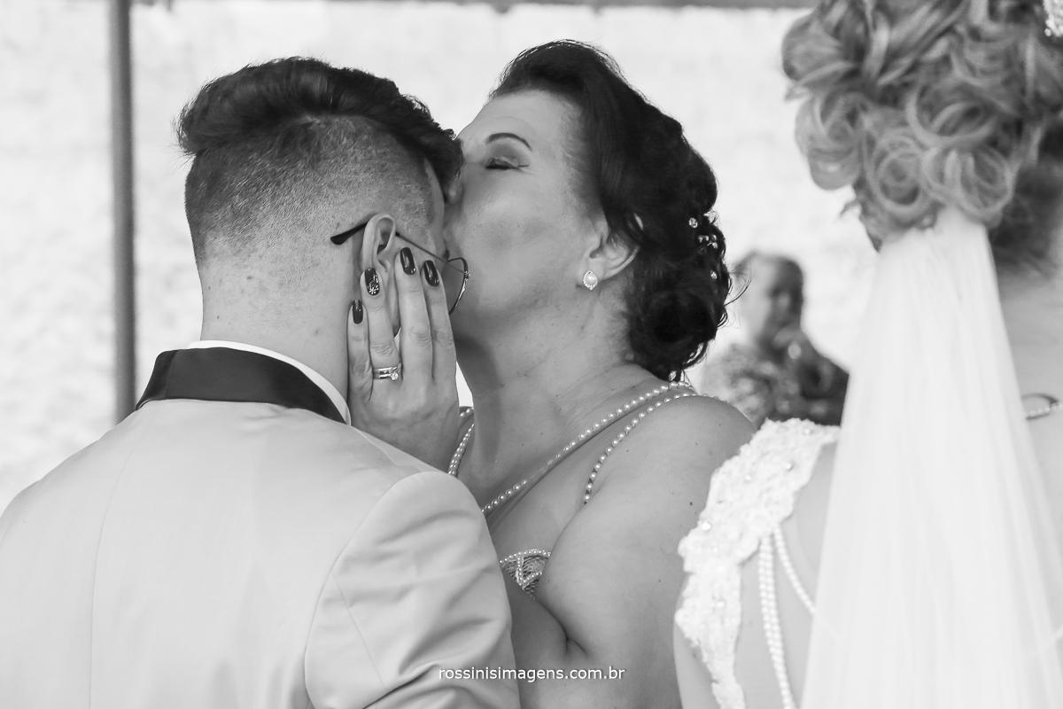 mãe do noivo beijando a testa do seu filho nos comprimento da cerimonia