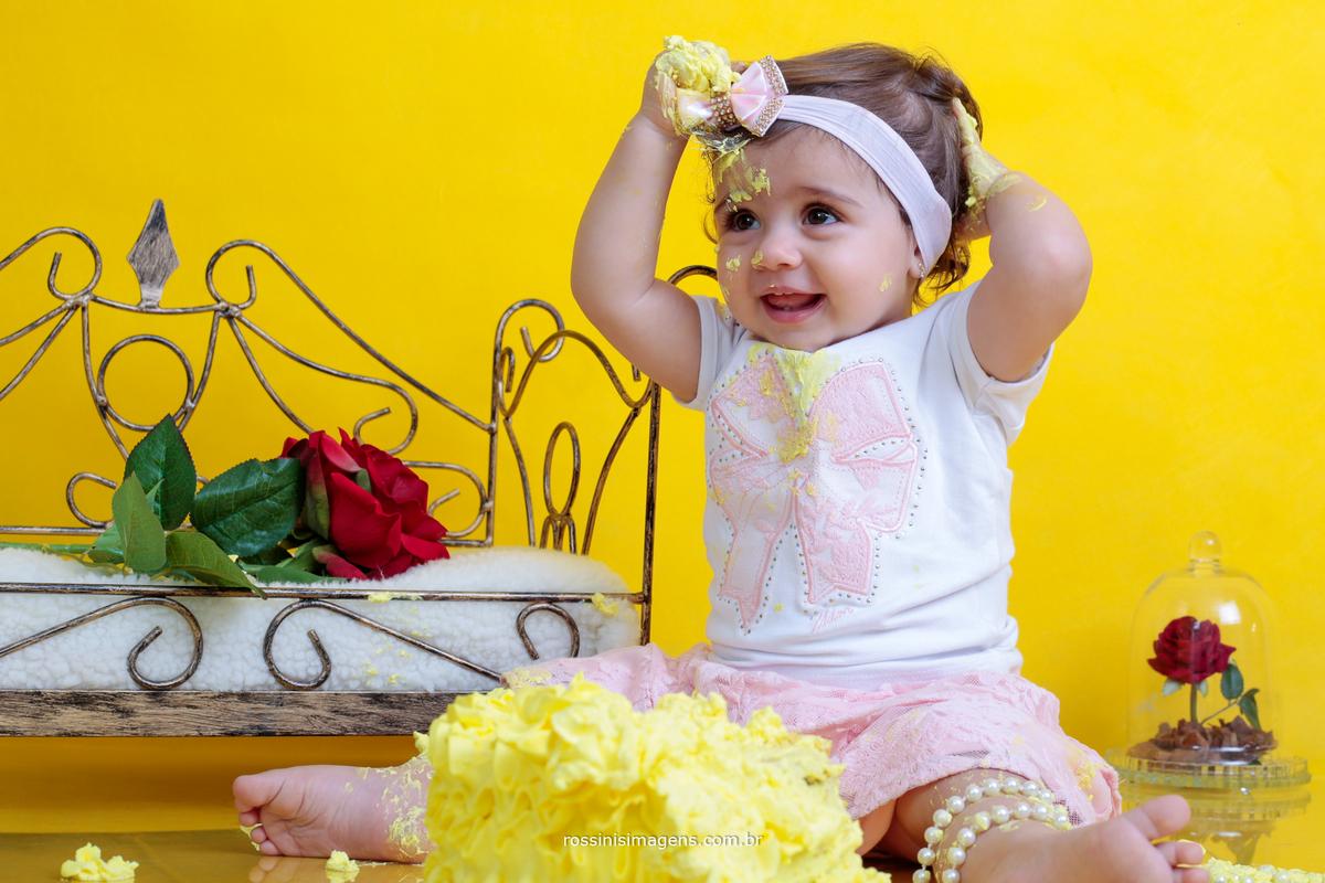 criança brincando com um lindo bolo no ensaio temático para o aniversário