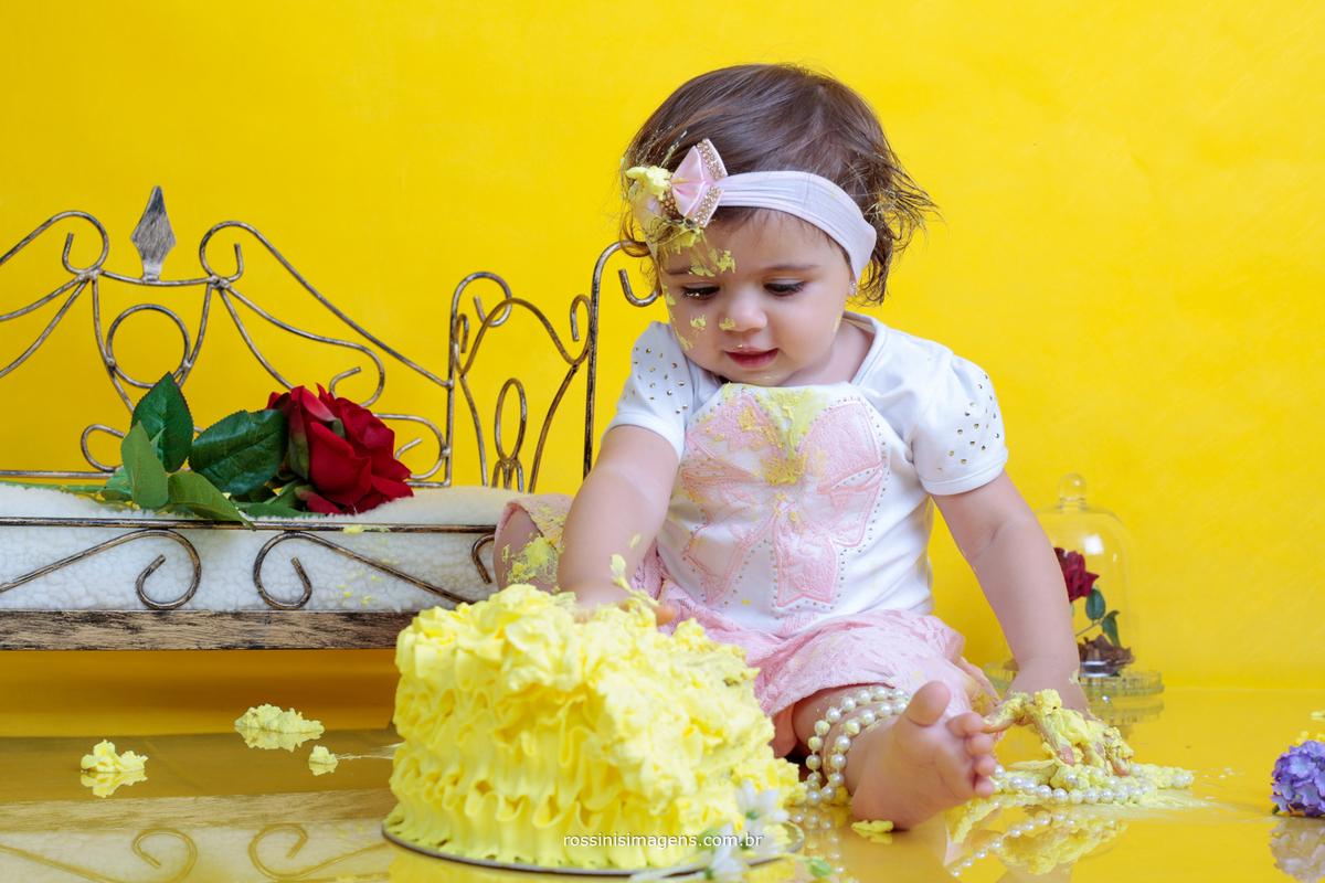 criança comendo bolo na sessão de fotos
