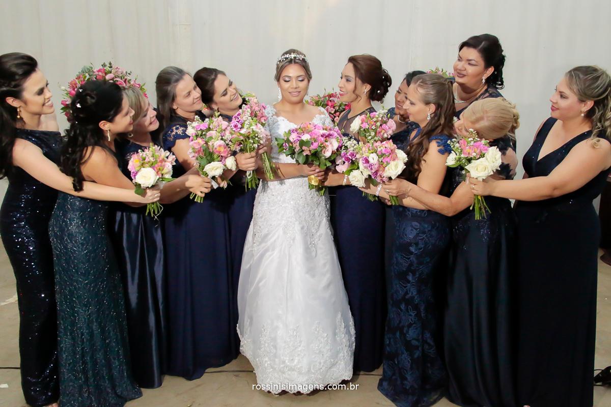 fotografia coletiva das madrinhas com buquê e a noiva na mesa do bolo, fotografo de casamento