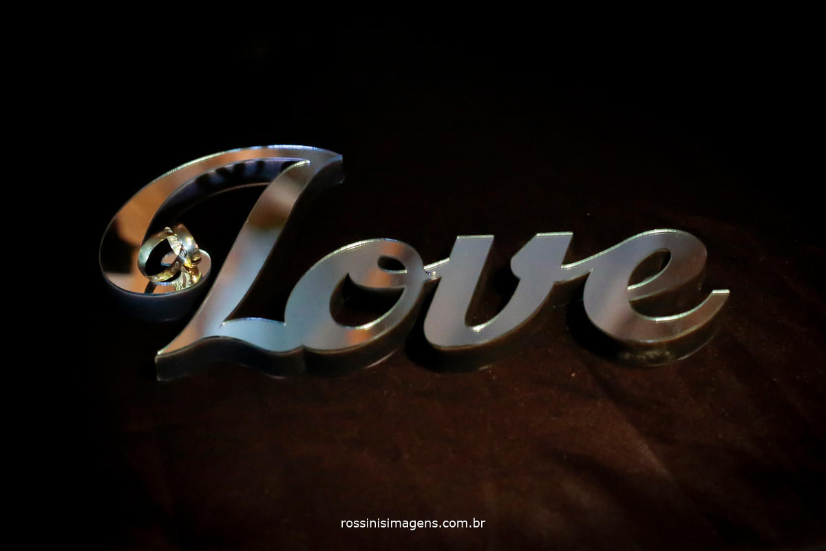 fotografia criativa de casamento, foto das alianças na palavra love em acrílico espelhado muito lindo