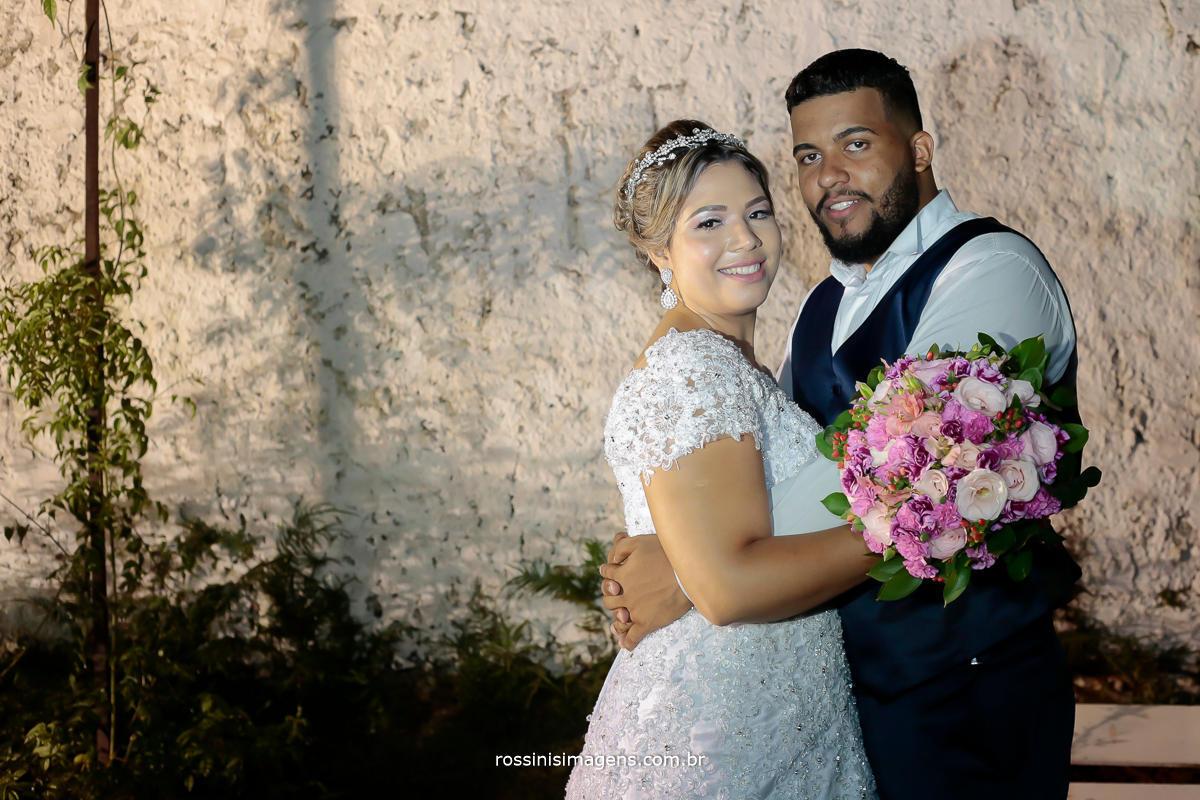 sessão de fotos de casal no casamento, externo noiva de branco e noivo de colete azul,  buquê tons de rosa