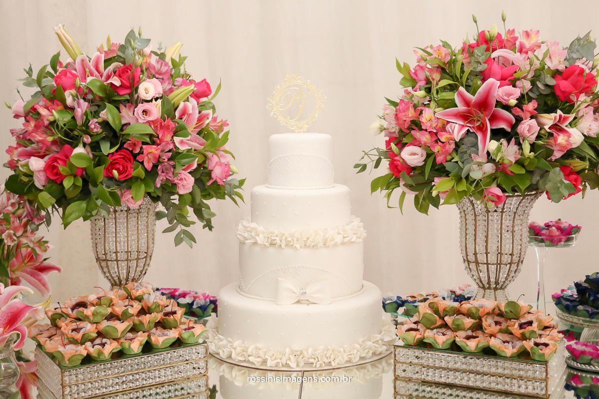 fotografia da linda mesa do bolo com flores em tons de rosa e bolo branco com topo de bolo em acrílico, muito lindo