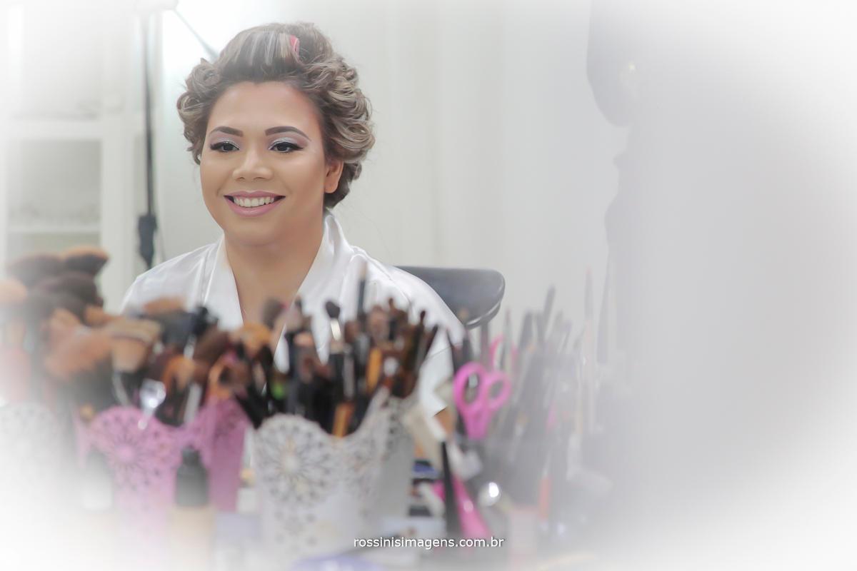 fotografia de noiva no espelho fazendo maquiagem