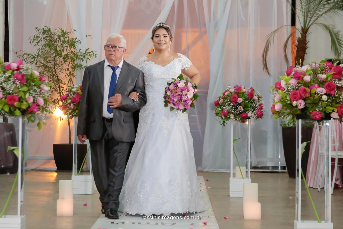 entrada da noiva de vestido branco tradição do casamento conduzida por seu pai sobre o lindo tapete com o salmo escrito