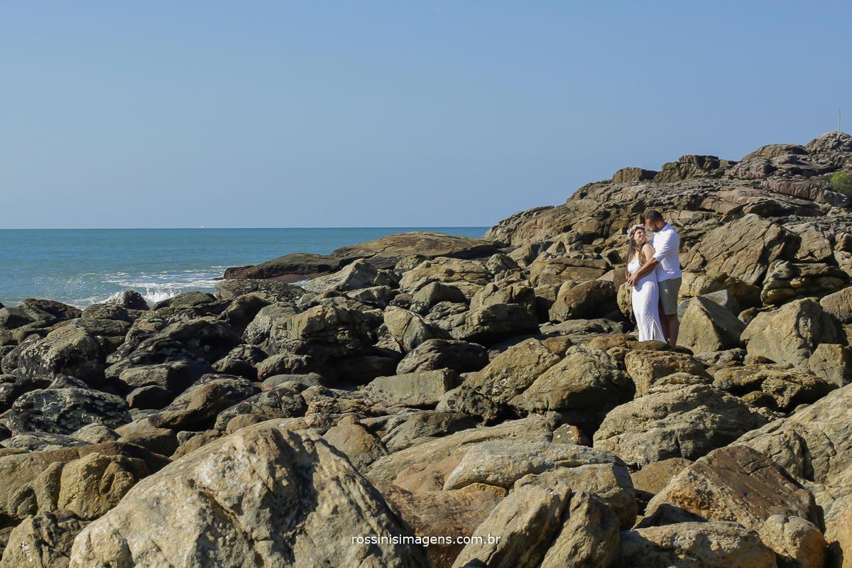 fotografia de ensaio pre casamento na praia, paisagem, casal abraçados em cima das pedras da praia de camburi,