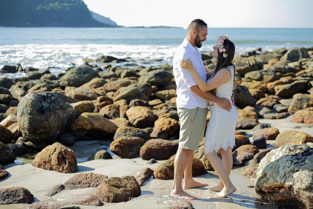 foto de casal abraçados sorrindo na praia em meio as pedras com o mar azul e um dia lindo de sol