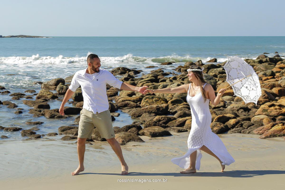 noivo roberto puxando a noiva amanda pela praia de camburi no lindo ensaio fotográfico realizado pela rossinis imagens - fotografia e video
