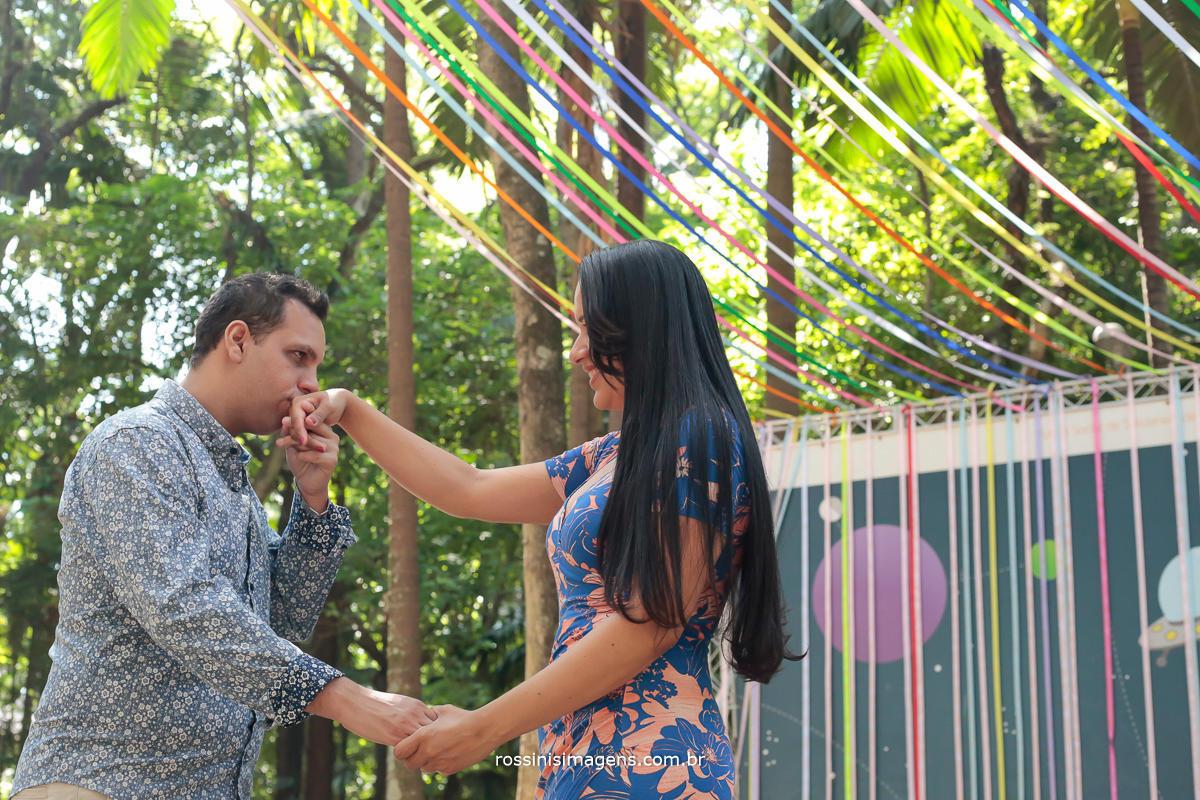 foto de casal no parque no ensaio noivo beijando a mão da noiva no dia lindo de sol com as lindas arvores