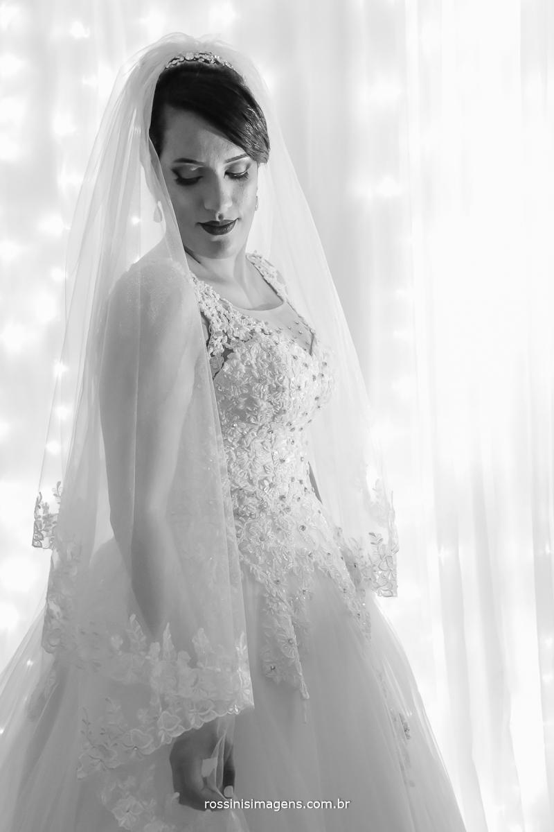 noiva pronta para ir para cerimonia vestido branco com muitas pedras um véu lindo com uma parede de led