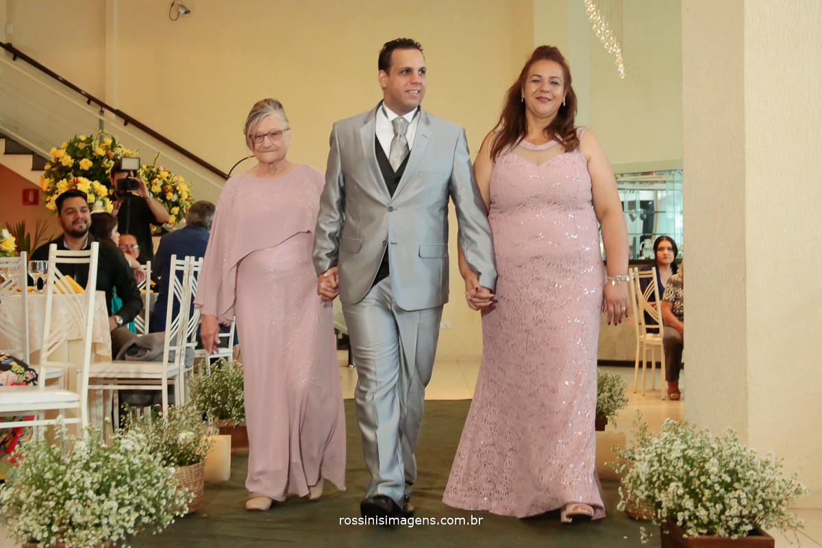 fotografia de cassamento noivo entrando com a mãe e avó