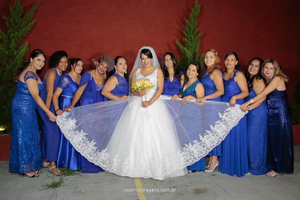 fotografia  da noiva com as madrinhas segurando a barra do vestido, madrinhas de azul royal e noiva de branco